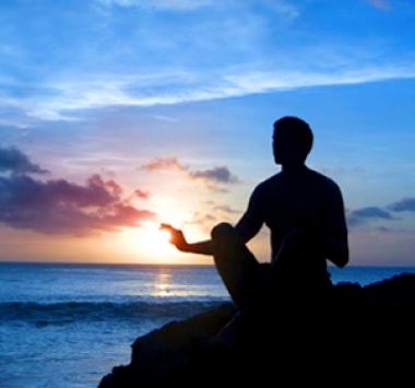 Image d'un coucher de soleil avec une personne en position de méditation